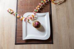 Kleiner Kuchen mit einer Geburtstagskerze auf Platte Lizenzfreies Stockbild
