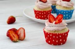 Kleiner Kuchen mit einer Platte von Muffins auf einem weißen Hintergrund lizenzfreie stockfotografie