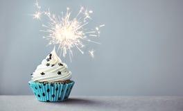 Kleiner Kuchen mit einer Wunderkerze Lizenzfreie Stockbilder