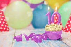 Kleiner Kuchen mit Geburtstagskerze für zehnten Geburtstag Stockbilder