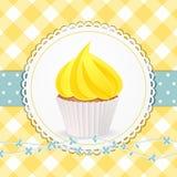 Kleiner Kuchen mit gelber Zuckerglasur auf gelbem Ginghamhintergrund Stockfotografie