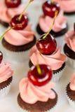 Kleiner Kuchen mit gepeitschter Sahne und Kirsche Stockfotografie