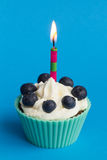 Kleiner Kuchen mit Kerze und Blaubeeren Stockfotografie