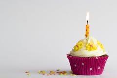 Kleiner Kuchen mit Kerze und gelben Zuckerblumen Lizenzfreies Stockbild