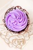 Kleiner Kuchen mit Lavendeloberseite in der festlichen Verpackung auf Beige Stockbild