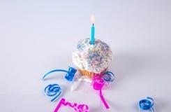 Kleiner Kuchen mit Lite-Kerze und Bänder auf weißem Hintergrund stockfotografie