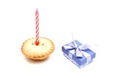 Kleiner Kuchen mit roter Geburtstagskerze und -geschenk auf Weiß Lizenzfreie Stockfotos