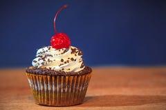 Kleiner Kuchen mit roter Kirsche auf die Oberseite Stockfoto