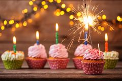 Kleiner Kuchen mit Wunderkerze auf altem hölzernem Hintergrund Lizenzfreie Stockbilder