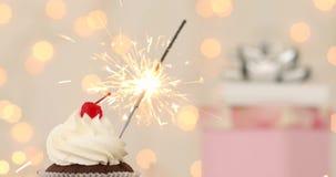 Kleiner Kuchen mit Wunderkerze auf beige Hintergrund stock video