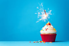 Kleiner Kuchen mit Wunderkerze auf Blau Lizenzfreies Stockbild