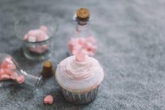 kleiner Kuchen und Flaschen mit rosa Schokoladenherzen, Eibische stockfotografie