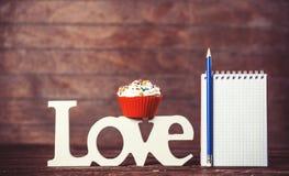 Kleiner Kuchen, Wort Liebe und Notizbuch Stockbilder