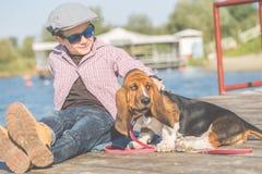 Kleiner lächelnder Junge, der mit seinem Hund durch den Fluss spielt stockfoto