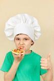 Kleiner lächelnder Junge im Chefhut schmeckt gekochte Pizza Lizenzfreies Stockbild