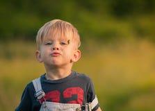 Kleiner Landwirt Boy Chews Playfully auf Gras Lizenzfreies Stockfoto