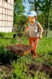 Kleiner Landwirt mit Schubkarre Lizenzfreies Stockfoto