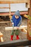 Kleiner lernbegieriger Junge, der ein hölzernes Brett sägt Wohnungsbau Li Lizenzfreies Stockfoto