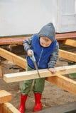 Kleiner lernbegieriger Junge, der ein hölzernes Brett sägt Wohnungsbau Li Stockfotografie