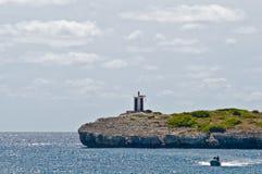 Kleiner Leuchtturm auf einem felsigen Ufer Lizenzfreies Stockfoto