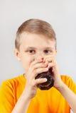 Kleiner lustiger blonder Junge, der frischen Kolabaum trinkt Lizenzfreie Stockfotos