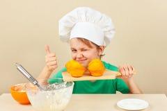 Kleiner lustiger Chef mit einem gekochten appetitanregenden Muffin Stockfotografie