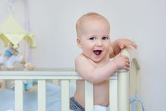 Kleiner lustiger Junge, der im Babybett und -c$lachen steht Lächelnder Ador lizenzfreie stockfotos