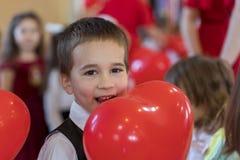 Kleiner lustiger Junge mit rotem Ballon Porträt eines lustigen Kindes, das einen großen roten Ballon gegen einen abstrakten Hinte Lizenzfreies Stockbild