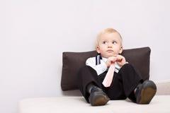 Kleiner müder Geschäftsmann, der auf dem Sofa sitzt Lizenzfreie Stockfotos