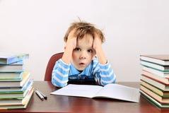 Kleiner müder Junge, der an einem Schreibtisch sitzt Stockbilder