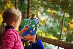 Kleiner Maler bei der Arbeit nahe Wasserfall Stockfotografie