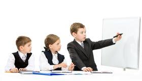 Kleiner Manager, der den kleinen Geschäftsleuten smth zeigt Lizenzfreie Stockfotos