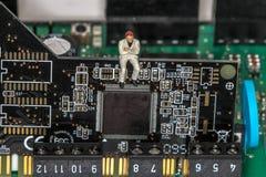 Kleiner Mann, der auf einem Motherboard stationiert stockfoto