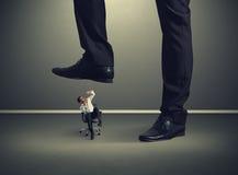Kleiner Mann unter großem Bein Stockfotos