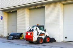 kleiner Minitraktor mit einem Blatt und einem Eimer f?r Stra?enreinigung ist am Tor einer gro?en Garage stockfotografie