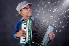 Kleiner Musiker, der das Akkordeon spielt Stockbild