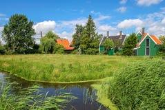 Kleiner Nebenfluss und ländliche Häuser im niederländischen Dorf lizenzfreie stockfotografie