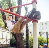 Kleiner netter blonder Junge, der draußen am Spielplatz, alleintraining mit Spaß, Lebensstilkinderkonzept hängt Lizenzfreie Stockfotos