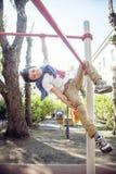 Kleiner netter blonder Junge, der draußen am Spielplatz, alleintraining mit Spaß, Lebensstilkinderkonzept hängt Stockbild