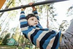 Kleiner netter blonder Junge, der draußen am Spielplatz, alleintraining mit Spaß, Lebensstilkinderkonzept hängt Stockfotografie