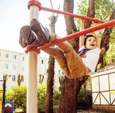 Kleiner netter blonder Junge, der draußen am Spielplatz, alleintraining mit Spaß, Lebensstilkinderkonzept hängt Stockbilder