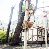 Kleiner netter blonder Junge, der draußen am Spielplatz, alleintraining mit Spaß, Lebensstilkinderkonzept hängt Stockfoto