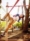 Kleiner netter blonder Junge, der draußen am Spielplatz, alleinzug hängt Stockbilder
