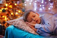 Kleiner netter blonder Junge, der unter dem Weihnachtsbaum und Träumen schläft Stockfoto