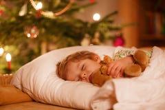 Kleiner netter blonder Junge, der unter Weihnachtsbaum schläft Stockbild