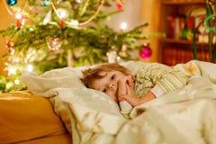 Kleiner netter blonder Junge, der unter Weihnachtsbaum schläft Lizenzfreies Stockbild