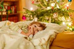 Kleiner netter blonder Junge, der unter Weihnachtsbaum schläft Stockfoto
