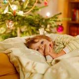 Kleiner netter blonder Junge, der unter Weihnachtsbaum schläft Stockbilder