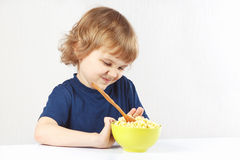 Kleiner netter blonder Junge lehnt ab, Getreide zu essen Stockfotografie