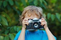 Kleiner netter blonder Junge mit einer Kamera schießt Sie Lizenzfreie Stockfotos